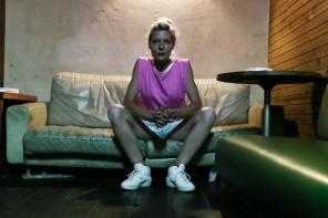 Brigitta Muntendorf sitzt auf einem Sofa in einer Bar